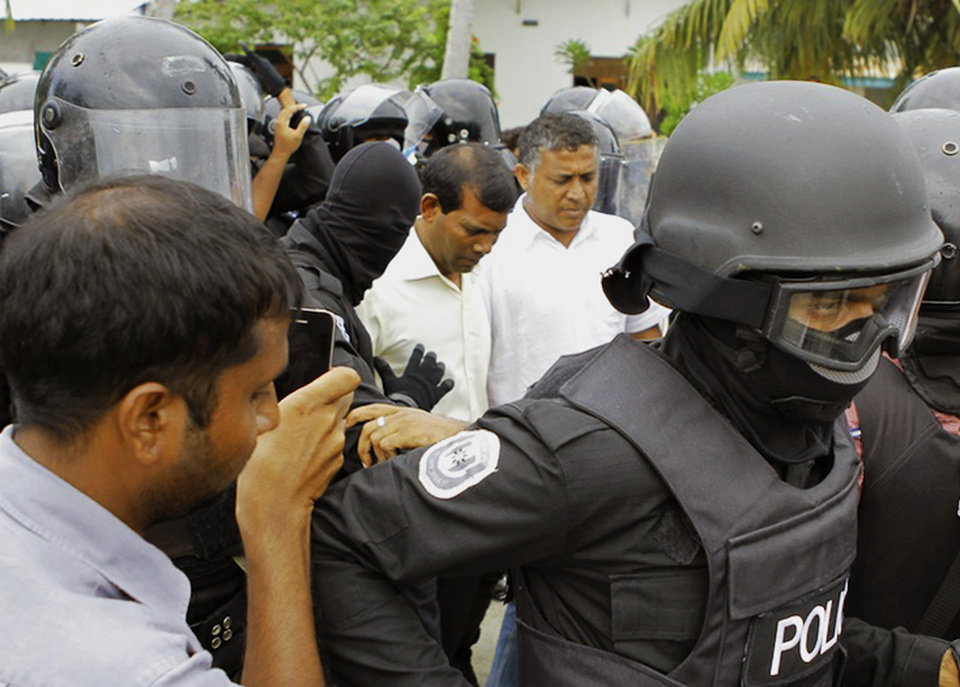 In this photo released by Maldivian Democratic Party Secretariat, Maldives' police personnel escort former President Mohamed Nasheed, center left, after he was arrested on Fares-Mathoda island, in the Gaaf Dhaal atoll, around 440 kilometers (273 miles) away from the capital Male, Maldives, Monday, Oct. 8, 2012. Police in the Maldives arrested Nasheed on Monday after he twice failed to appear before a court to face charges that he illegally ordered the arrest of a judge while in office. (AP Photo/Maldivian Democratic Party Secretariat)