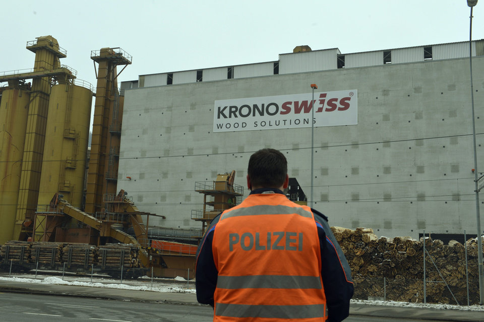 A police stands in front of a wood-processing company in Menznau, central Switzerland, Wednesday, Feb. 27, 2013, where several people were killed in a shooting. Police in Lucerne canton (state) said in a statement that the shooting occurred shortly after 9 a.m. at the premises of Kronospan, a company in the small town west of Lucerne. They said there were �several dead and several seriously injured people� and that rescue services were deployed and the scene sealed off. (AP Photo/Keystone, Urs Flueeler)