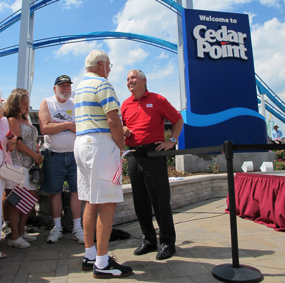 Photo - In a Wedneday, July 2, 2014 photo, Matt Ouimet, chief executive of Cedar Fair Entertainment Co., greets a guest at Cedar Point amusement park,in Sandusky, Ohio. Ouimet has spent his first two years with the company adding rides and attractions that appeal to families and not just thrill seekers. (AP Photo John Seewer)