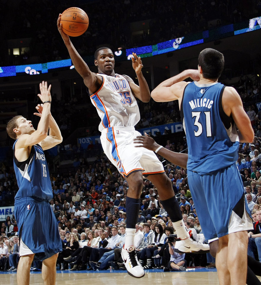 Photo - Oklahoma City's Kevin Durant (35) passes the ball between Luke Ridnour (13) and Darko Milicic (31) of Minnesota during the NBA basketball game between the Minnesota Timberwolves and the Oklahoma City Thunder at the Oklahoma City Arena, Monday, November 22, 2010, in Oklahoma City. The Thunder won, 117-107. Photo by Nate Billings, The Oklahoman