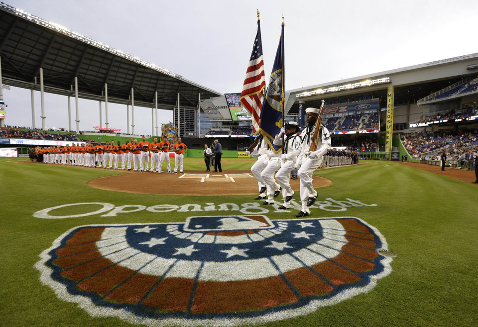 Photo - The color guard matches onto the field during a pre-game ceremony for opening night baseball game between the Miami Marlins and Colorado Rockies, Monday, March 31, 2014, in Miami. (AP Photo/Lynne Sladky)