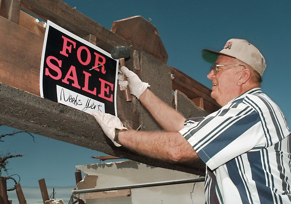MAY 3, 1999 TORNADO: Tornado damage: FOR SALE-NEEDS WORK, Russell Taylor hangs a sign on the house of his brother-in-law, Harold and Lorene File, at 2405 Edgewood in Moore Highland Park housing addition.