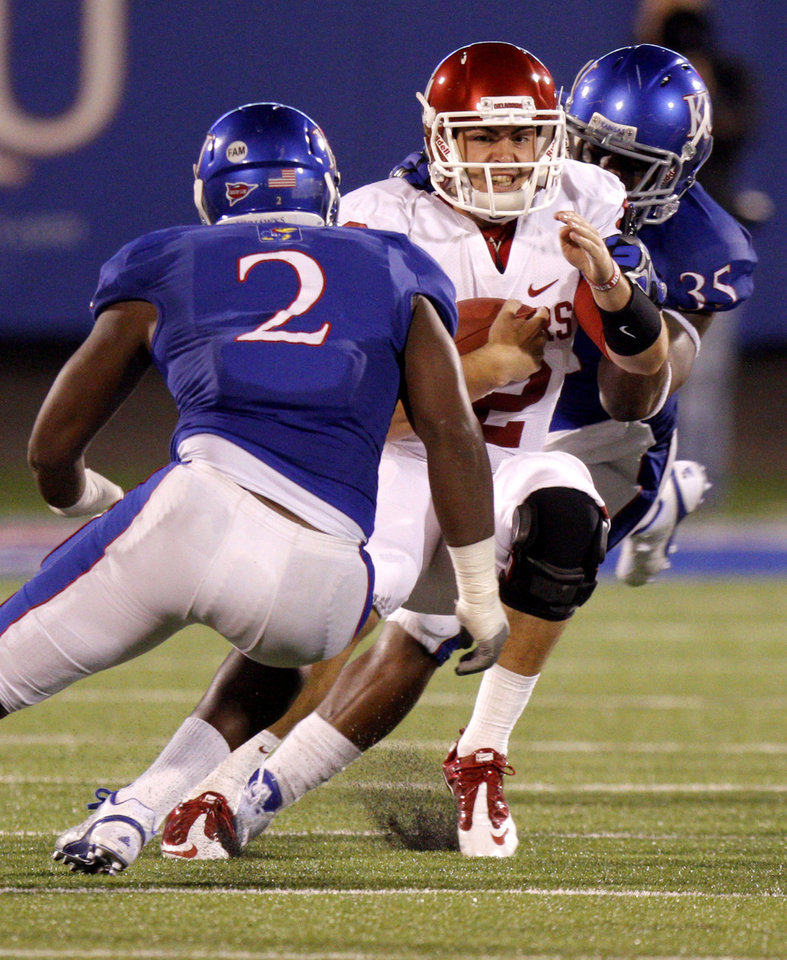 Photo - Oklahoma's Landry Jones (12) is brought down between Kansas' Darius Willis (2) and Toben Opurum (35) during the college football game between the University of Oklahoma Sooners (OU) and the University of Kansas Jayhawks (KU) at Memorial Stadium in Lawrence, Kansas, Saturday, Oct. 15, 2011. Photo by Bryan Terry, The Oklahoman