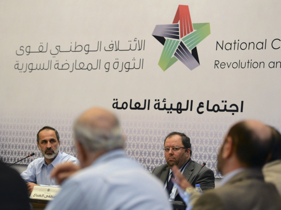 Photo - Head of the new Syrian National Coalition for Opposition and Revolutionary Forces Mouaz al-Khatib, rear-left, speaks during a meeting in Istanbul, Turkey, Monday, March 2013.  Syria's main opposition coalition began a push Monday to form an interim government to provide services to people living in parts of the country now controlled by rebel forces.  Arabic writing at centre reads, General Assembly Meeting.(AP Photo)