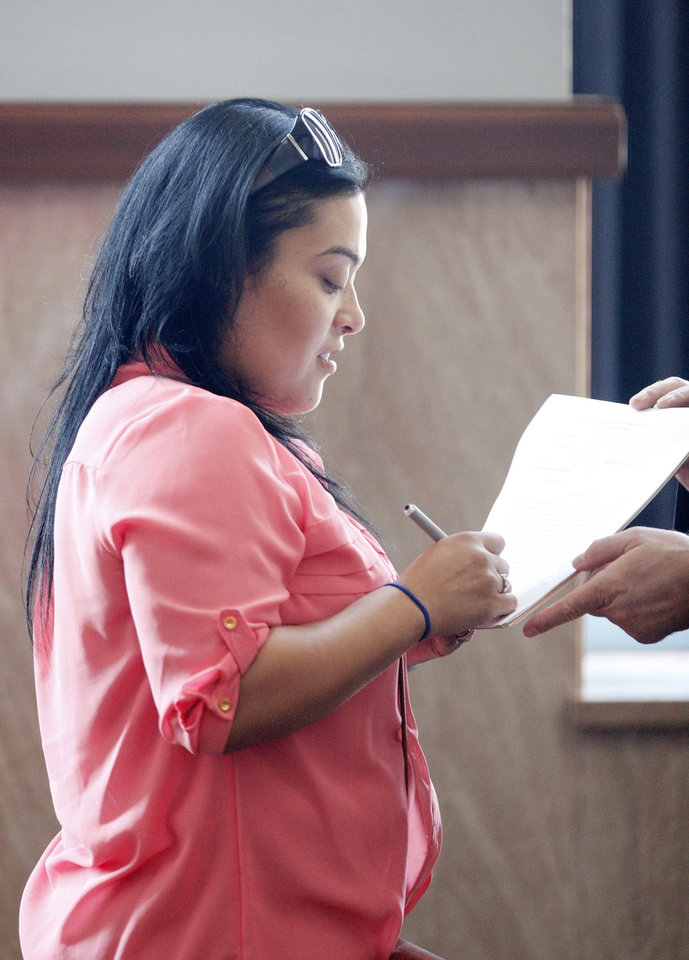 Photo - Monica Salazar Orozco, of Jourdanton, Texas,  signs papers in the courtroom while waiting to plead guilty Wednesday at the Oklahoma County Courthouse. Salazar-Orozco, a dental receptionist, and her mother, Elizabeth Hinojosa, a dental assistant, both pleaded guilty to practicing dentistry without a license. Photo by Paul B. Southerland, The Oklahoman  PAUL B. SOUTHERLAND - PAUL B. SOUTHERLAND