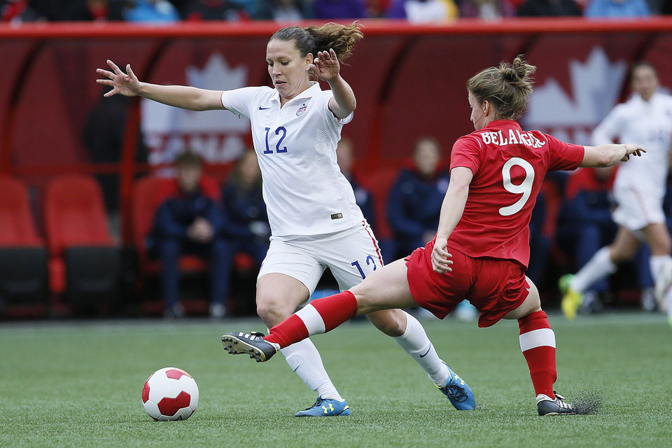 Photo - United States midfielder Lauren Holiday (12) drives forward as Canada's forward Josée Belanger (9) defends during first half of an exhibition soccer match in Winnipeg, Manitoba, Thursday, May 8, 2014. (AP Photo/The Canadian Press, John Woods)