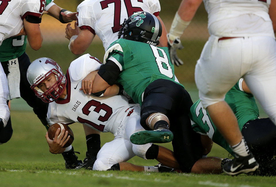 Photo - Weatherford's Garrett Gaunt is brought down by Bobby Sweeney of Bishop McGuinness during their high school football game in Oklahoma City, Friday, Sept. 20, 2013. Photo by Bryan Terry, The Oklahoman