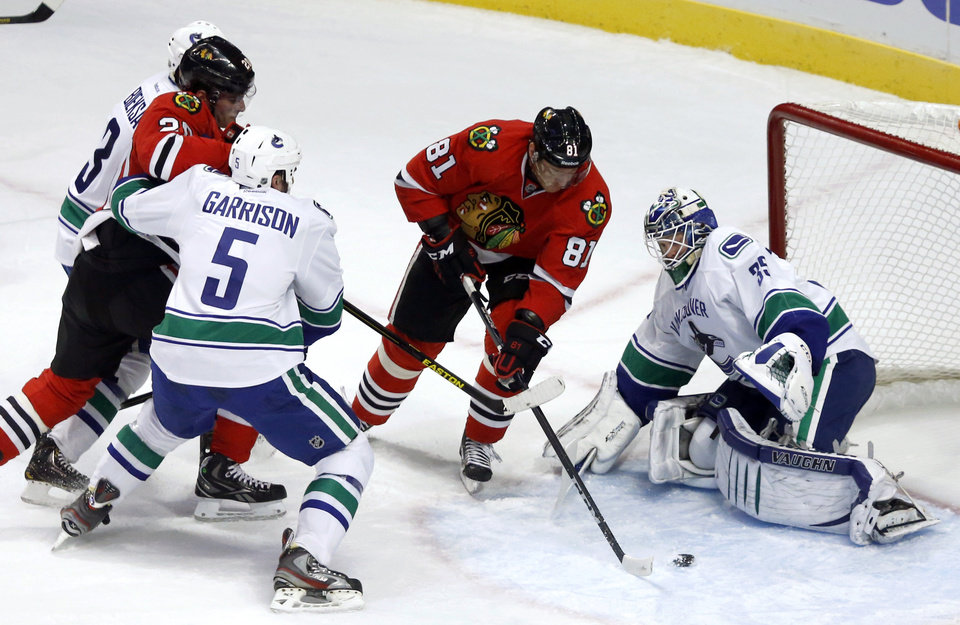 Photo - Chicago Blackhawks right wing Marian Hossa (81), from Slovakia, splits the defense of Vancouver Canucks' Kevin Bieksa (3), Jason Garrison (5) and goalie Cory Schneider to score his second goal in the second period of an NHL hockey game Tuesday, Feb. 19, 2013 in Chicago.  Blackhawks' Brandon Saad watches the play. (AP Photo/Charles Rex Arbogast)