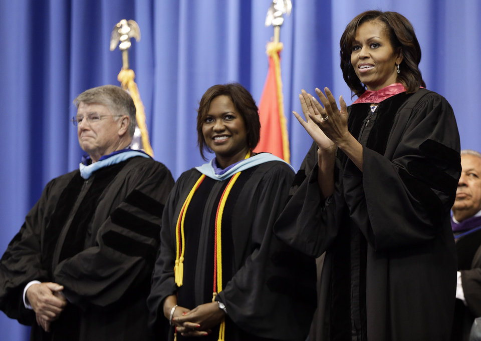 First lady Michelle Obama, right, applauds as students enter the arena for the commencement ceremony of Martin Luther King, Jr. Academic Magnet High School on Saturday, May 18, 2013, in Nashville, Tenn. With her are Dr. Jesse Register, left, director of Nashville schools, and Schunn Turner, principal, center. (AP Photo/Mark Humphrey)