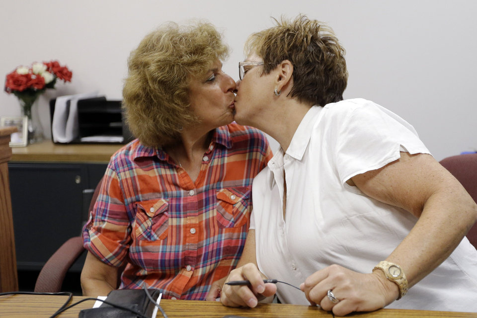 Photo - Ellen Toplin, right, and Charlene Kurland kiss as they obtain a marriage license at a Montgomery County office despite a state law banning such unions, Wednesday, July 24, 2013, in Norristown, Pa.  The chairman of the Montgomery County commissioners, Democrat Josh Shapiro, said he supports same-sex marriage and was ready for the county to defend the stance in court.   (AP Photo/Matt Rourke)