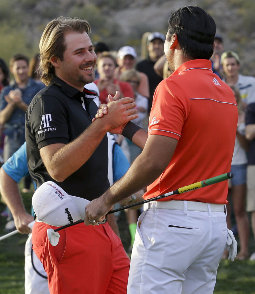 Photo - Jason Day, of  Australia, right, shakes hands on the 23rd hole after winning his championship match against Victor Dubuisson, of France, during the Match Play Championship golf tournament, Sunday, Feb. 23, 2014, in Marana, Ariz. (AP Photo/Ted S. Warren)