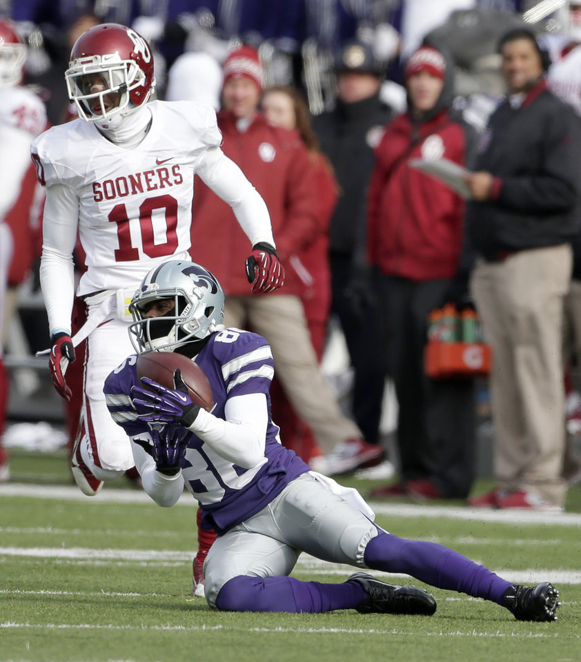 Kansas State tight end Cody Small (80) catches a long pass for a first down under pressure from Oklahoma defensive back Quentin Hayes (10) during the first half of an NCAA college football game Saturday, Nov. 23, 2013 in Manhattan, Kan. (AP Photo/Charlie Riedel)