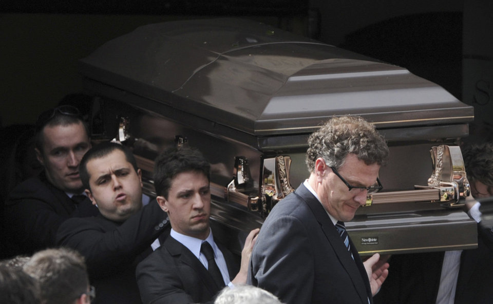 Photo - Pallbearers carry the coffin of Christopher Lane to the funeral hearse at St. Therese's Church in Melbourne, Australia, Wednesday. Lane died Aug. 16 in Duncan. (AP Photo/AAP Image, Julian Smith)  Julian Smith - AP