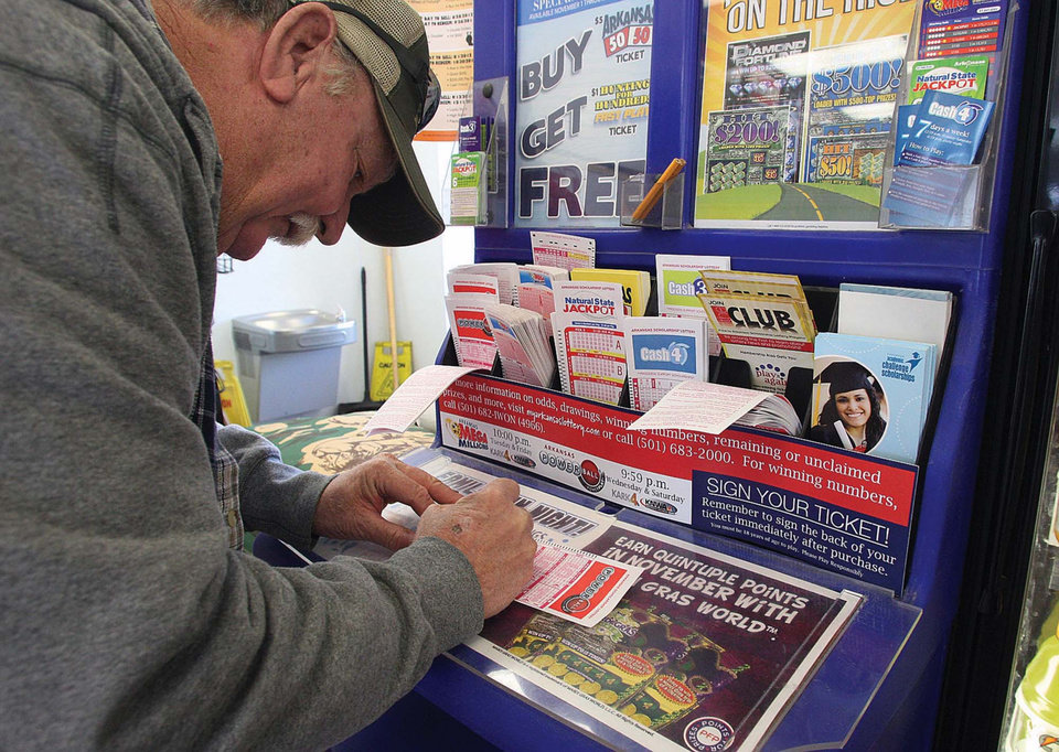 Photo - A customer at the Express Way on East Main Street in El Dorado, Ark. fills in his lucky numbers on Wednesday, Nov. 28, 2012, for a chance to win the record setting Powerball jackpot. As Americans went on a ticket-buying spree, the Powerball jackpot rose to $550 million Wednesday, enticing many people who rarely, if ever, play the lottery to purchase a shot at the second-largest payout in U.S. history. (AP Photo/The El Dorado News-Times, Michael Orrell)