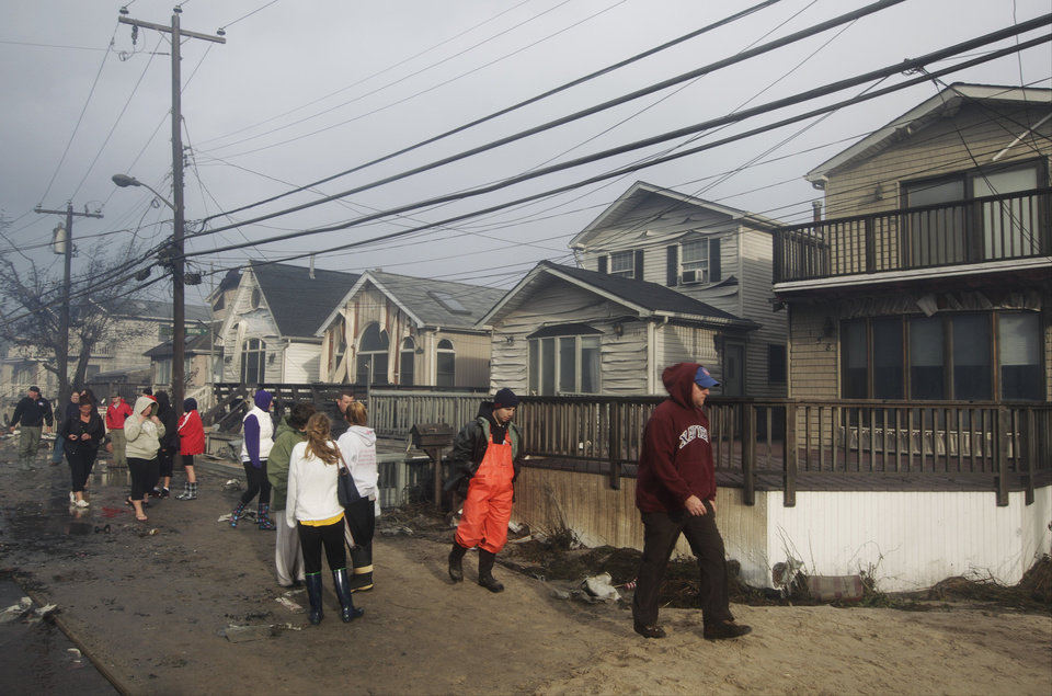 Photo -   Residents assess damage caused by a fire at Breezy Point, in the New York City borough of Queens Tuesday, Oct. 30, 2012, in New York. The fire destroyed between 80 and 100 houses Monday night in the flooded neighborhood. More than 190 firefighters have contained the six-alarm blaze fire, but they are still putting out some pockets of fire. (AP Photo/Frank Franklin II)
