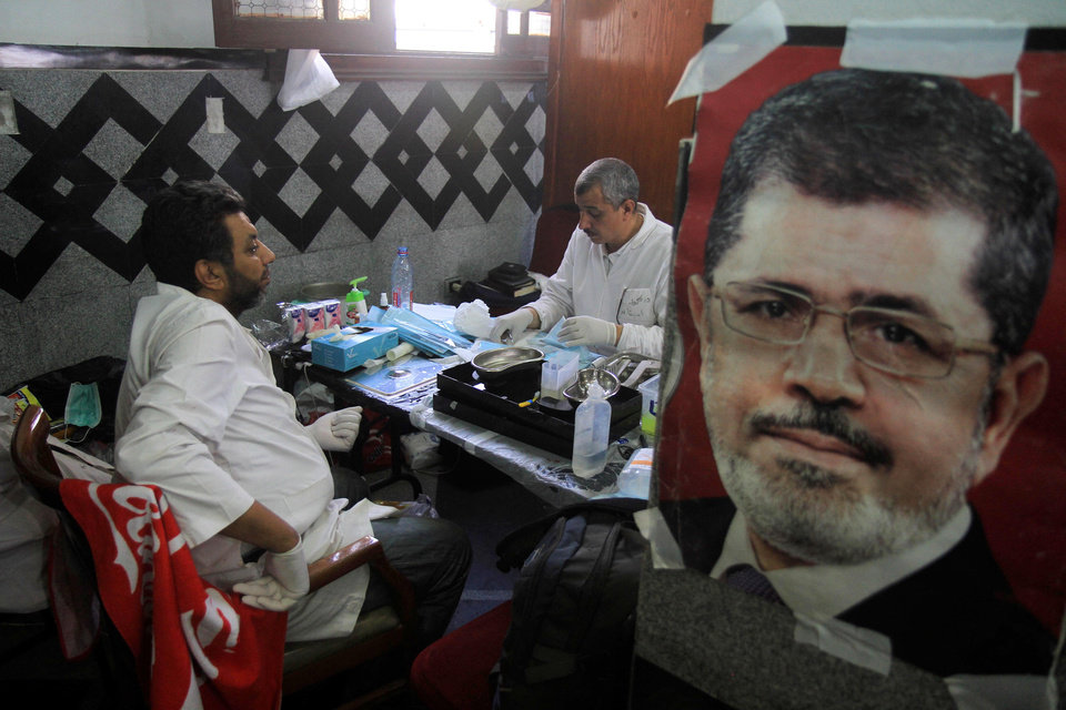 Photo - Medics sitin a makeshift hospital after Egyptian soldiers and police opened fire on supporters of the ousted President Mohammed Morsi, on the photo,  early Monday in Cairo,  Egypt, Monday, July 8 , 2013. The violence left dozens  people killed outside the Republican Guard military building in Cairo where demonstrators had been holding a sit-in, government officials and witnesses said. (AP Photo/ Ahmed Gomaa )