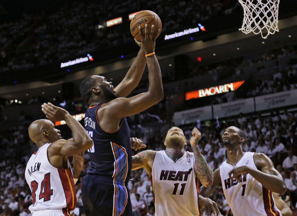 Photo - Charlotte Bobcats' Al Jefferson (25) shoots in front of Miami Heat's Ray Allen (34), Chris Andersen (11) and Chris Bosh (1) during the second half in Game 1 of an opening-round NBA basketball playoff series, Sunday, April 20, 2014, in Miami. The Heat defeated the Bobcats 99-88. (AP Photo/Lynne Sladky)