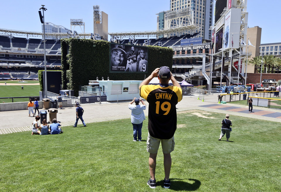 Photo - A Tony Gwynn fan shoots a photo of the big screen outside Petco Park that displays images of Gwynn who passed away Monday, June 16, 2014, in San Diego. Gwynn, an eight time National League batting champion with the San Diego Padres and a member of Baseball Hall of Fame, died Monday from cancer. He was 54. (AP Photo/Lenny Ignelzi)