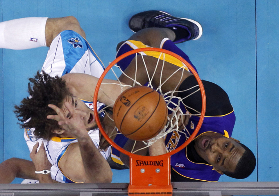 Photo - New Orleans Hornets center Robin Lopez, left, goes to the basket against Los Angeles Lakers center Dwight Howard during the first half of an NBA basketball game in New Orleans, Wednesday, March 6, 2013. (AP Photo/Gerald Herbert)