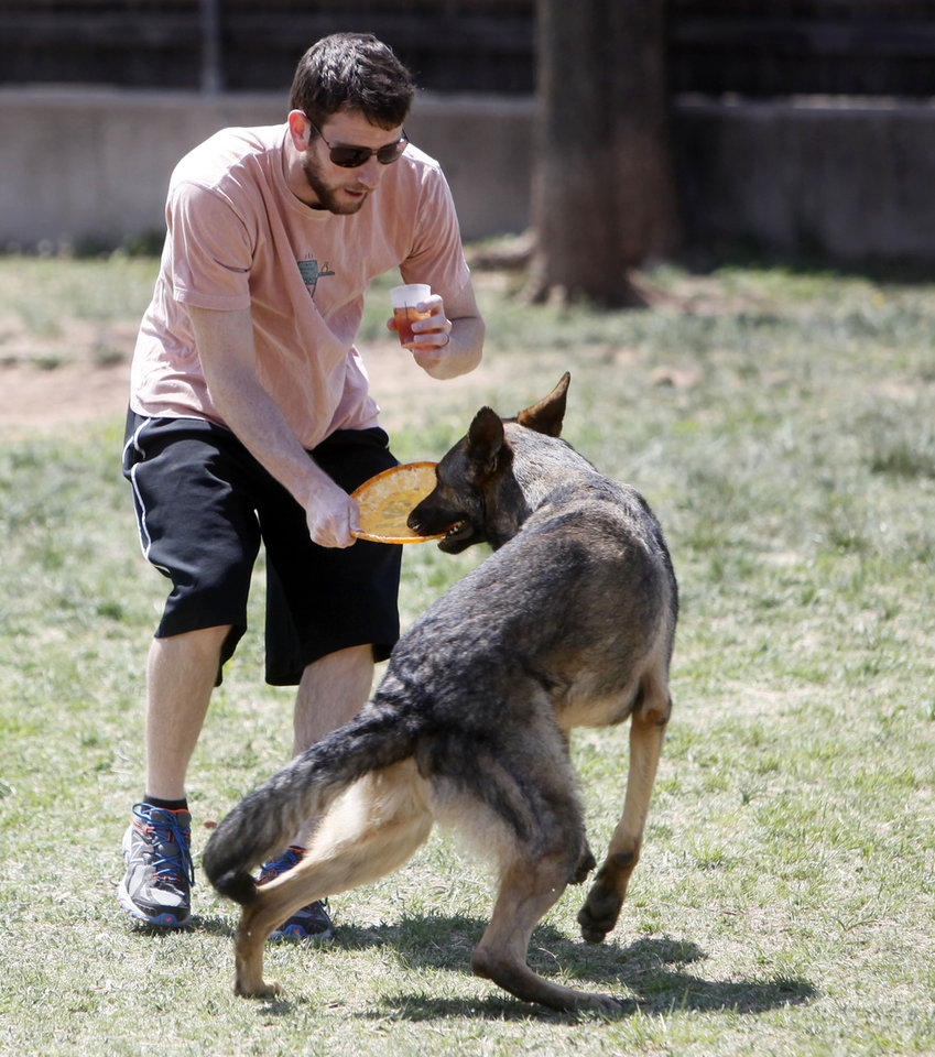 Photo -  Chris Holden, of Edmond, grabs the Frisbee from his dog, Otis, as they play at the dog park. PHOTO BY K.T. KING, THE OKLAHOMAN   KT King -