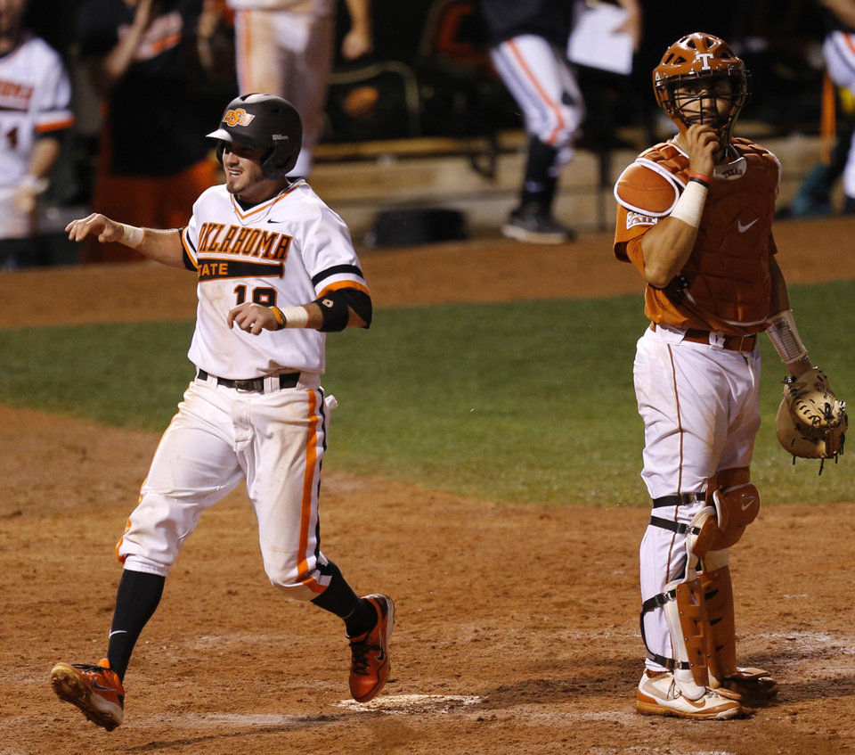 Photo - OSU's Aaron Cornell smiles as he runs home past Texas' Tres Barrera in the eighth inning of a Big 12 Tournament baseball game between Oklahoma State University and the University of Texas at Chickasaw Bricktown Ballpark in Oklahoma City, Saturday, May 24, 2014. Photo by Bryan Terry The Oklahoman