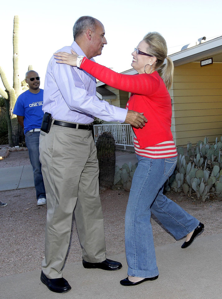 Former U.S. Surgeon General and Democratic senatorial candidate Richard Carmona greets former Democratic Arizona state senator and Arizona congressional candidate Kyrsten Sinema, right, in a neighborhood in Mesa, Ariz., Monday, Nov. 5, 2012. Carmona is running against Republican Rep. Jeff Flake for the Senate seat vacated by retiring Republican Jon Kyl while Sinema is seeking Arizona's 9th Congressional District seat against challenger Vernon Parker. (AP Photo/Matt York)