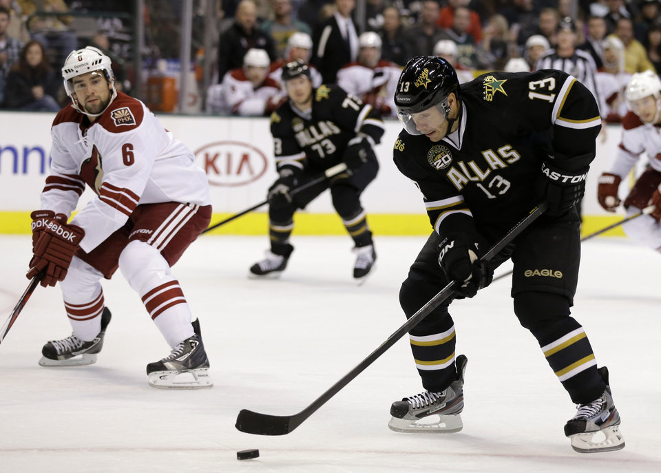 Dallas Stars\' Ray Whitney (13) prepares to take a shot on-goal under pressure fro Phoenix Coyotes\' David Schlemko (6) in the first period of an NHL hockey game on Friday, Feb. 1, 2013, in Dallas. (AP Photo/Tony Gutierrez)