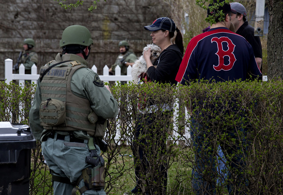People and a pet gather outside a home as heavily armed police officers did house to house search on a street in Watertown, Mass. Friday, April 19, 2013, as a massive search continued for one of two suspects in the Boston Marathon bombing. A second suspect died in the early morning hours after an encounter with law enforcement. (AP Photo/Craig Ruttle) ORG XMIT: MACC116