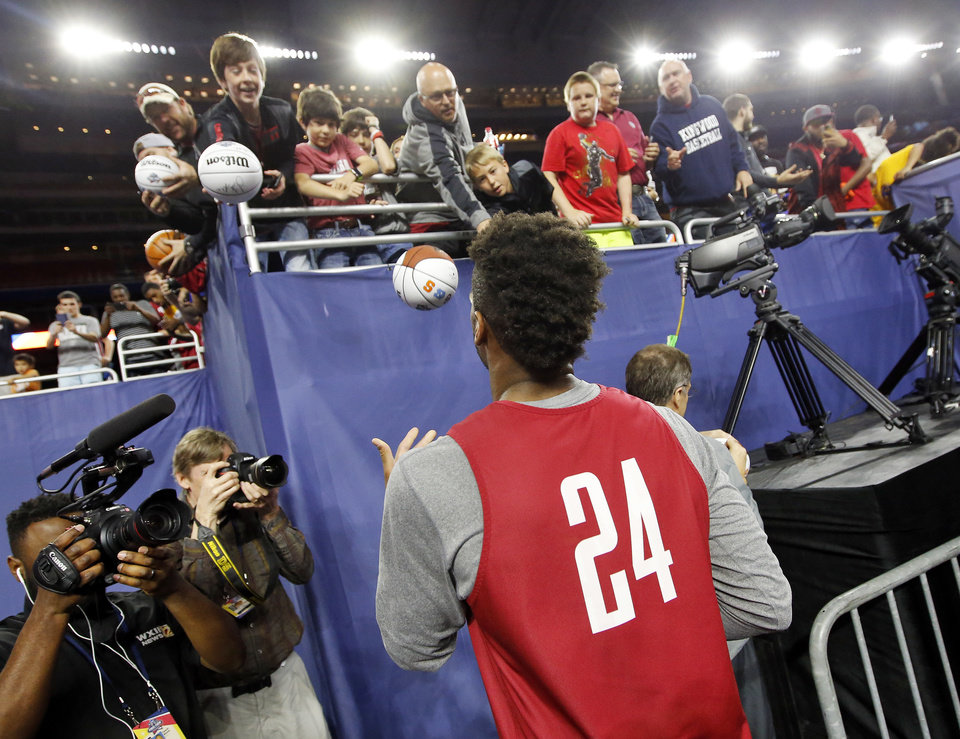 Photo - Oklahoma's Buddy Hield (24) tosses an autograph ball to a fan after signing it during Final Four Friday before the national semifinal between the Oklahoma Sooners and the Villanova Wildcats in the NCAA Men's Basketball Championship at NRG Stadium in Houston, Friday, April 1, 2016. OU will play Villanova in the Final Four on Saturday. Photo by Nate Billings, The Oklahoman