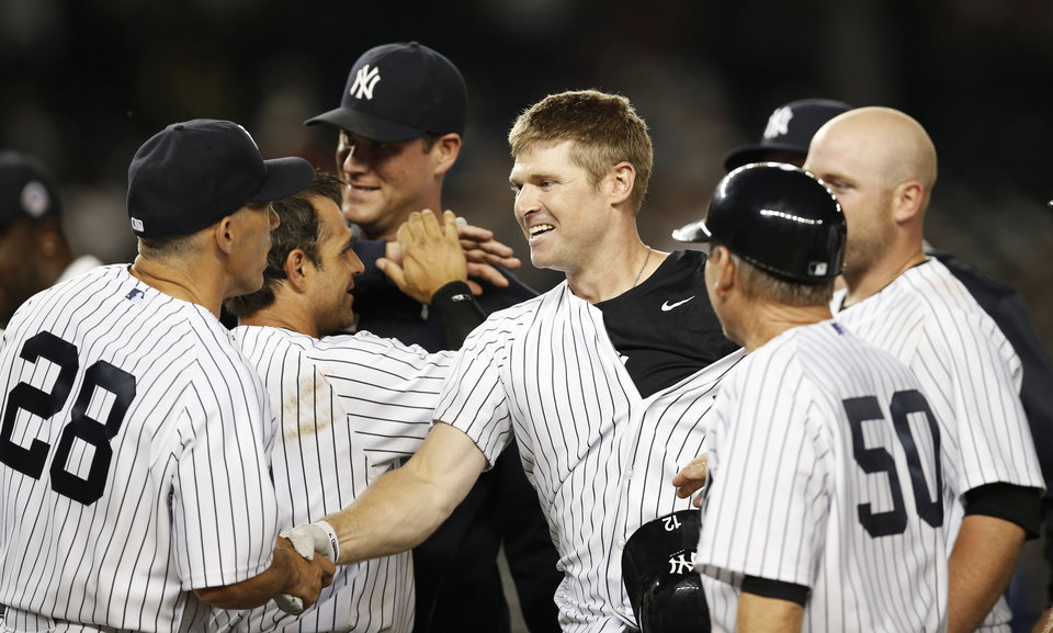 Photo - New York Yankees manager Joe Girardi (28) congratulates newly acquired New York Yankees Chase Headley, center, who hit a 14th inning, game-wimnning, walk-off RBI single to lift the Yankees to a 2-1 victory over the Texas Rangers in a baseball game at Yankee Stadium in New York, Wednesday, July 23, 2014. (AP Photo)