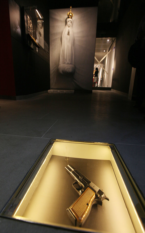 Photo - The Browning HP 9mm handgun that would-be assassin Ali Agca used against Pope John Paul II injuring him in a May 13, 1981 attack in St. Peter's Square in Rome, is pictured at the new Pope Museum in Wadowice, Poland, Monday, April 7, 2014. The gun is among items on display at a new multimedia museum in the Pope's birth house in Wadowice. The museum opens this week, ahead of the Vatican ceremony during which he will be made a saint April 27. (AP Photo/Czarek Sokolowski)
