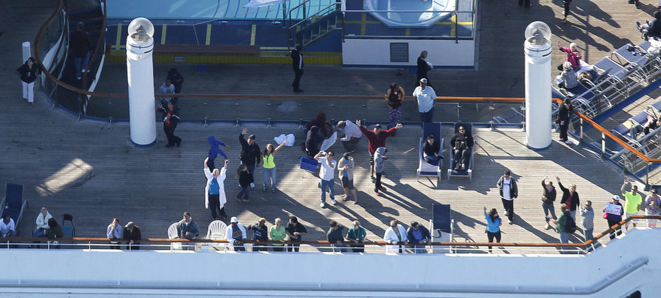 Photo - In this aerial photo, passengers congregate on an upper deck of the disabled Carnival Lines cruise ship Triumph as it is towed to harbor off Mobile Bay, Ala., Thursday, Feb. 14, 2013. The ship with more than 4,200 passengers and crew members has been idled for nearly a week in the Gulf of Mexico following an engine room fire. (AP Photo/Gerald Herbert)