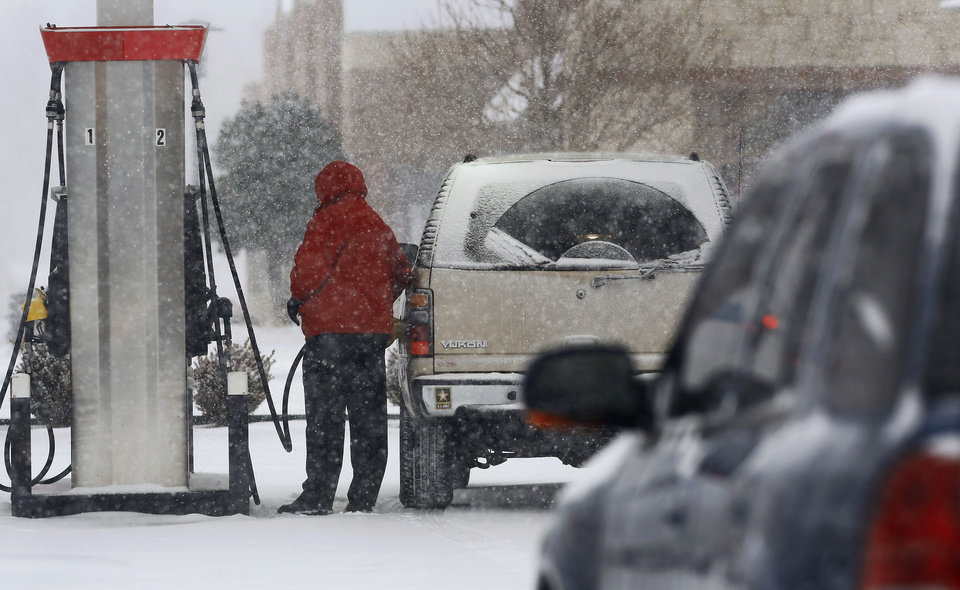 Photo - A motorist adds gasoline to their car at a convenience store at SE 15 and Key Blvd. in Midwest City. Snow began falling in central Oklahoma around 7 Sunday morning, Feb. 2, 2014.   Photo by Jim Beckel, The Oklahoman