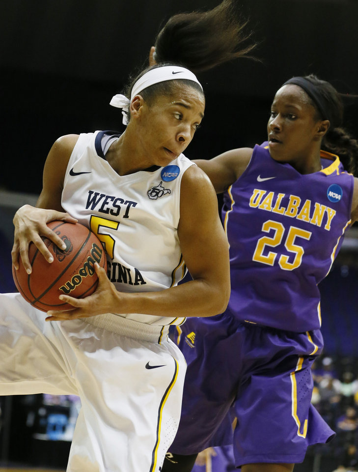 Photo - West Virginia forward Averee Fields (5) looks for an open teammate after pulling down a rebound past the defense of Albany forward Shereesha Richards (25) in the first half of an NCAA college basketball first-round tournament game on Sunday, March 23, 2014, in Baton Rouge, La. (AP Photo/Rogelio V. Solis)