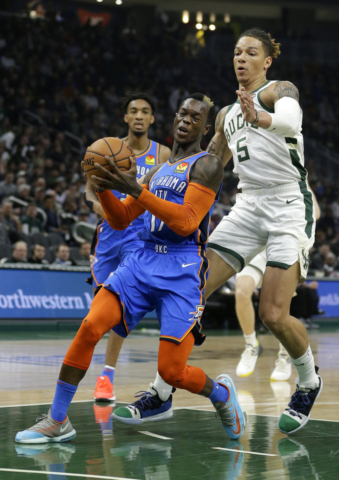 Photo - Oklahoma City Thunder's Dennis Schroder is fouled on a drive to the basket by Milwaukee Bucks' D.J. Wilson during the first half of an NBA basketball game Wednesday, April 10, 2019, in Milwaukee. (AP Photo/Aaron Gash)