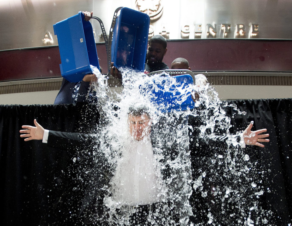 Photo - Tim Leiweke, President and CEO of Maple Leaf Sports Entertainment participates in the ALS Ice Bucket Challenge as Nazem Kadri, rear left, of the Toronto Maple Leafs, Amir Johnson, center, of the Toronto Raptors and  Jermain Defoe, right, of Toronto FC dump ice water on Leiweke in Toronto on Wednesday, Aug. 20, 2014. (AP Photo/The Canadian Press, Nathan Denette)