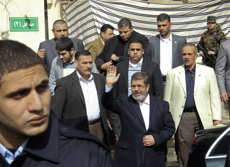 Photo - Egyptian President Mohammed Morsi, center, waves after attending Friday prayers in Cairo, Egypt, Feb. 1, 2013. Thousands of Egyptians marched across the country, chanting against the rule of the Islamist President Mohammed Morsi, in a fresh wave of protests Friday, even as cracks appeared in the ranks of the opposition after its political leaders met for the first time with the rival Muslim Brotherhood. (AP Photo/Jihan Nasr, Shorouk Newspaper)  EGYPT OUT