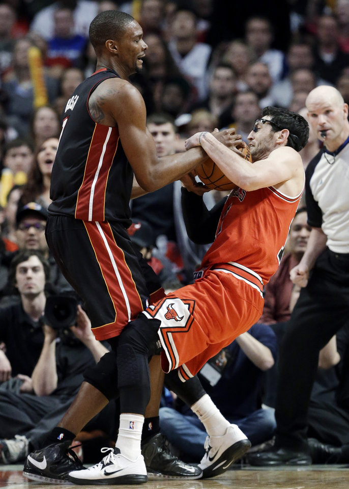 Photo - Chicago Bulls guard Kirk Hinrich, right, and Miami Heat center Chris Bosh wrestle for a rebound during the second half of an NBA basketball game in Chicago on Wednesday, March 27, 2013. The Bulls won 101-97, ending the Heat's 27-game winning streak. (AP Photo/Nam Y. Huh)