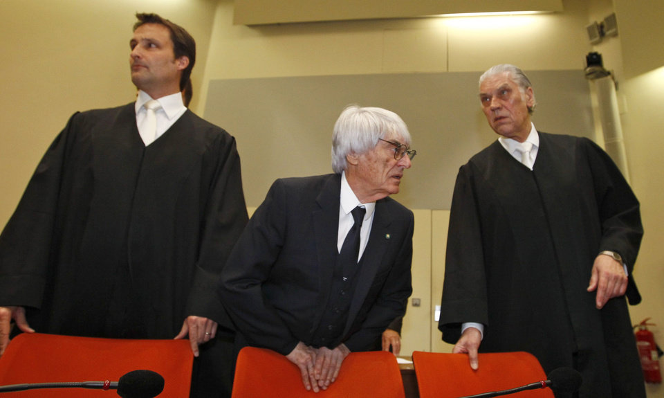 Photo - F1 CEO Bernie Ecclestone, center, stands with his lawyers Sven Thomas, right, and Norbert Scharf as he arrives in the  court in Munich, southern Germany, Thursday, April 24, 2014. Ecclestone is charged with bribery and incitement to breach of trust