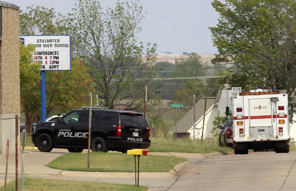Photo - Police and fire vehicles are parked outside Stillwater Junior High School in Stillwater, Okla., Wednesday, Sept. 26, 2012. A 13-year-old student shot and killed himself in a hallway at an Oklahoma junior high school before classes began Wednesday, police said,   (AP Photo/Sue Ogrocki) ORG XMIT: OKSO109