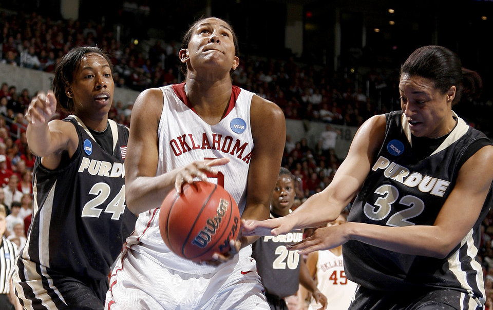 Photo - OU's Ashley Paris looks to the basket between Purdue's Lakisha Freeman, left, and Lindsay Wisdom-Hylton during the NCAA women's basketball regional  tournament finals between Oklahoma and Purdue at the Ford Center in Oklahoma City, Tuesday, March 31, 2009.  Photo by Bryan Terry, The Oklahoman