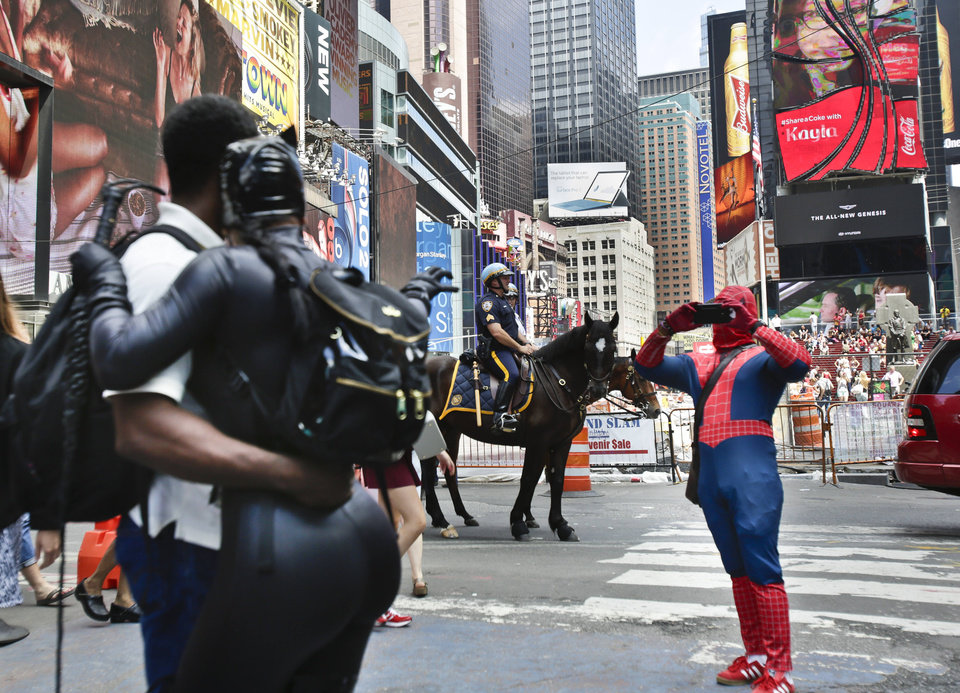 Photo - A Times Square visitor poses for photos with an iconic costumed character, Monday, July 28, 2014, in New York. New York Mayor Bill de Blasio said Monday that he believes the people wearing character costumes in Times Square should be licensed and regulated. (AP Photo/Rachelle Blidner)