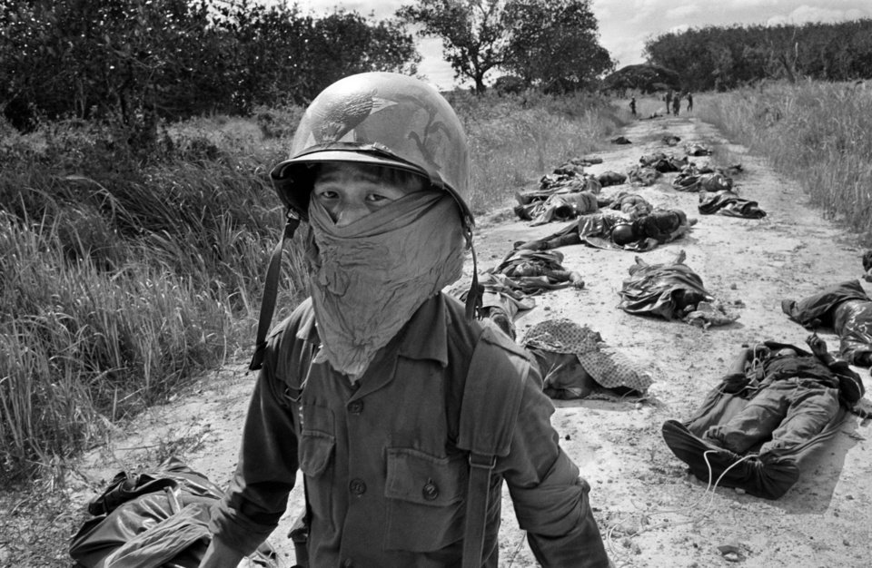 Photo -   FILE - In this Nov. 27, 1965 file photo taken by Associated Press photographer Horst Faas, a Vietnamese litter bearer wears a face mask to keep out the smell as he passes the bodies of U.S. and Vietnamese soildiers killed in fighting against the Viet Cong at the Michelin rubber plantation, about 45 miles northeast of Saigon. Faas, a prize-winning combat photographer who carved out new standards for covering war with a camera and became one of the world's legendary photojournalists in nearly half a century with The Associated Press, died Thursday May 10, 2012. He was 79. (AP Photo/Horst Faas, File)