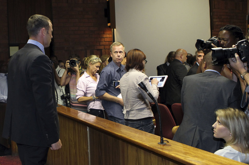 Photo - Olympic athlete Oscar Pistorius, left,  stands as the judges leaves the court, during his bail application at the magistrate court, in Pretoria, South Africa, Tuesday, Feb. 19, 2013.  Pistorius fired into the door of a small bathroom where his girlfriend was cowering after a shouting match on Valentine's Day, hitting her three times, a South African prosecutor said Tuesday as he charged the sports icon with premeditated murder. The magistrate ruled that Pistorius faces the harshest bail requirements available in South African law. He did not elaborate before a break was called in the session. (AP Photo/Themba Hadebe)