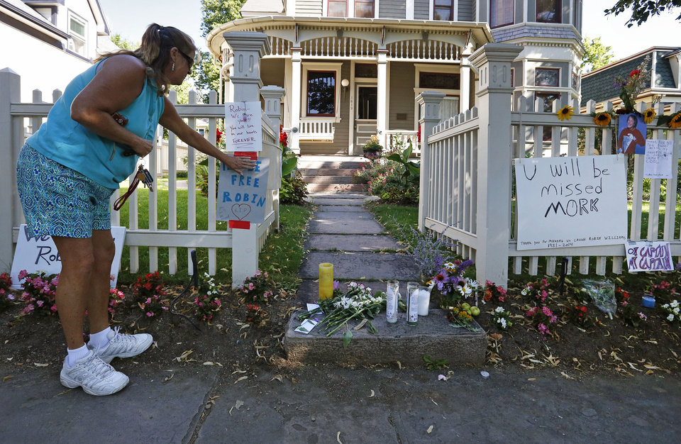 "Photo - Boulder resident Wendy Darling tapes up a sign that reads ""Fly Be Free Robin,"" as she pays tribute to Robin Williams at a makeshift memorial outside the home where the 80s TV series ""Mork & Mindy,""  was set, in Boulder, Colo., Tuesday Aug. 12, 2014. Williams, the Academy Award winner and comic supernova whose explosions of pop culture riffs and impressions dazzled audiences for decades and made him a gleamy-eyed laureate for the Information Age, died Monday in an apparent suicide. He was 63. (AP Photo/Brennan Linsley)"