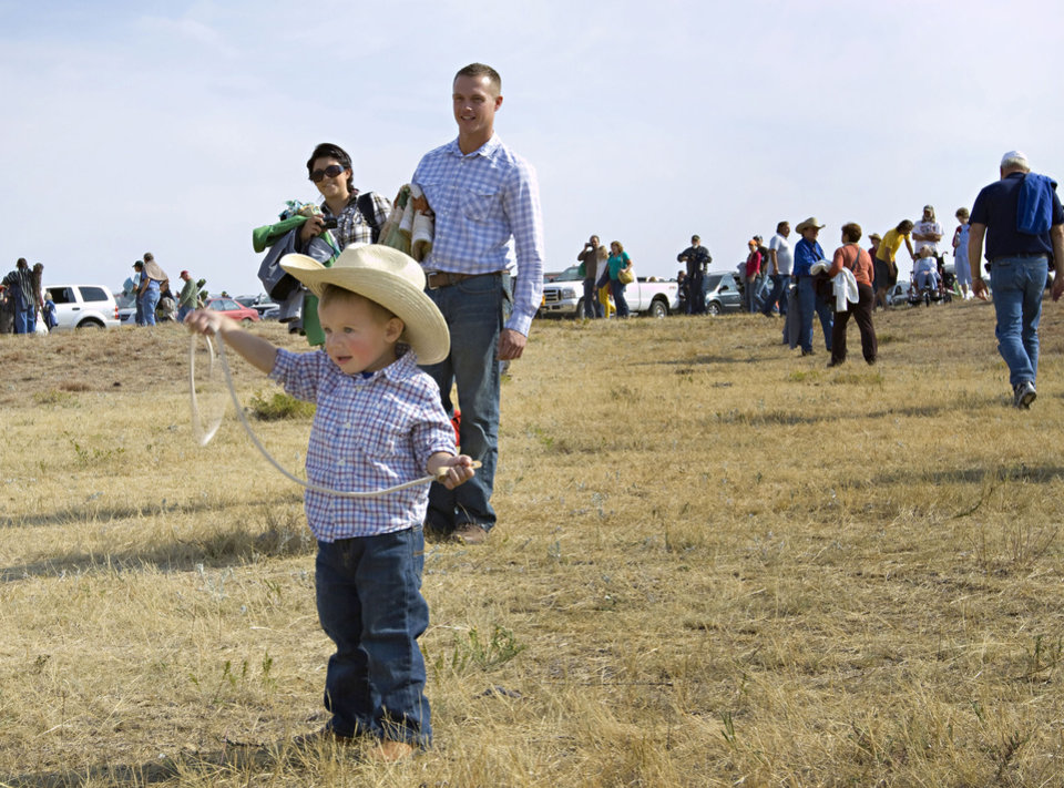Photo -   Two-year-old Jameson Maxwell plays cowboy as parents Maria and Ryan Maxwell of Rock Valley, Iowa, look on, Monday, Sept. 24, 2012 in Custer, S.D. The family was among more than 14,000 spectators from across the world who gathered to watch the herding of about 1,000 buffalo during the 47th annual Buffalo Roundup in western South Dakota's Custer State Park. (AP Photo/Kristi Eaton)