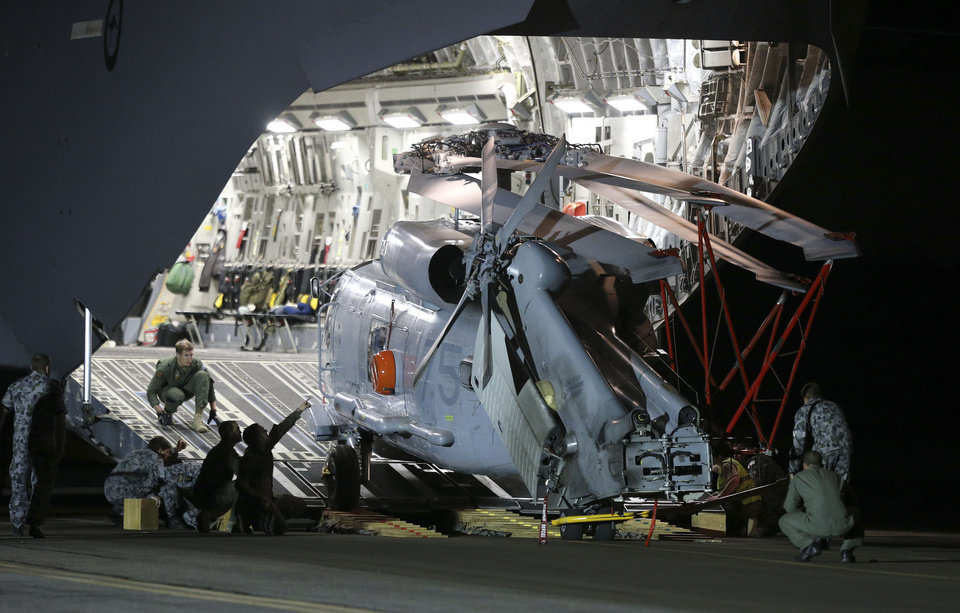 Photo - Ground crew unload a Sea Hawk helicopter from a Royal Australia Air Force C-17 after it landed at RAAF Base Pearce to help with the search for the missing Malaysia Airlines Flight MH370 in Perth, Australia, Friday, March 28, 2014. Australian officials moved the search area for the lost Malaysian jetliner 1,100 kilometers (680 miles) to the northeast Friday, following a new analysis of radar data, and a plane quickly found objects that a ship set out to investigate. (AP Photo/Rob Griffith)
