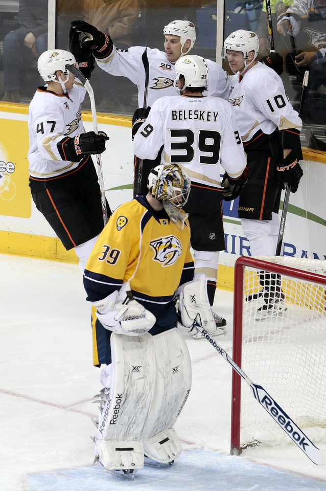 Photo - Anaheim Ducks center Ryan Getzlaf, top center, celebrates with Hampus Lindholm (47), of Sweden, Matt Beleskey (39) and Corey Perry (10) after scoring his second goal of the game against Nashville Predators goalie Marek Mazanec (39), of the Czech Republic, in the second period of an NHL hockey game Thursday, Jan. 9, 2014, in Nashville, Tenn. (AP Photo/Mark Humphrey)