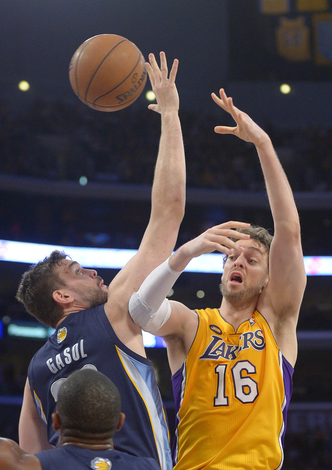 Los Angeles Lakers forward Pau Gasol, right, of Spain, passes the ball as Memphis Grizzlies center Marc Gasol, of Spain, defends during the first half of their NBA basketball game, Friday, April 5, 2013, in Los Angeles. (AP Photo/Mark J. Terrill)