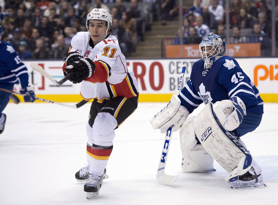 Photo - Calgary Flames centre Mikael Backlund (11) tries to deflect the puck in front of Toronto Maple Leafs goaltender Jonathan Bernier during first period NHL action in Toronto on Tuesday April 1, 2014. (AP Photo/The Canadian Press, Frank Gunn)